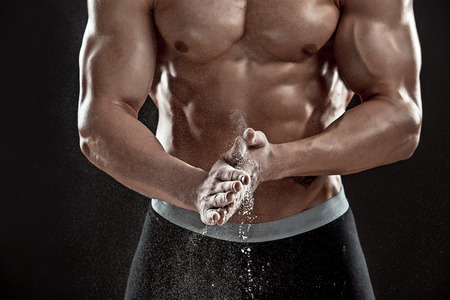 dynamically: young muscular man preparing to hand lifting heavy weight. White talcum dynamically scatters in different directions. Close-up