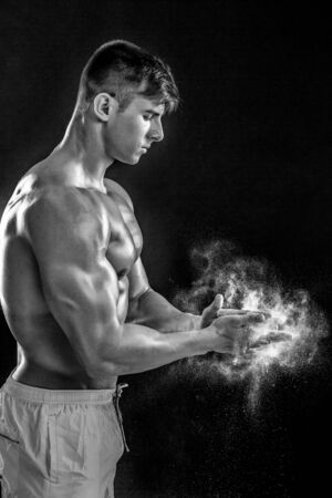 dynamically: young muscular man preparing to hand lifting heavy weight. White talcum dynamically scatters in different directions.. Black and white. stands sideways Stock Photo