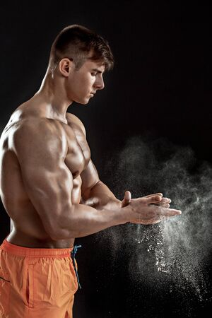 scatters: young muscular man preparing to hand lifting heavy weight. White talcum dynamically scatters in different directions. stands sideways Stock Photo