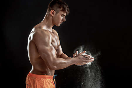 dynamically: young muscular man preparing to hand lifting heavy weight. White talcum dynamically scatters in different directions. stands sideways Stock Photo