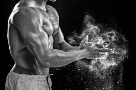 scatters: young muscular man preparing to hand lifting heavy weight. White talcum dynamically scatters in different directions.. Black and white. stands sideways. Close-up