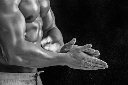 dynamically: young muscular man preparing to hand lifting heavy weight. White talcum dynamically scatters in different directions.. Black and white. stands sideways. Close-up