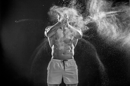 dynamically: young muscular man preparing to hand lifting heavy weight. White talcum dynamically scatters in different directions. Black and white Stock Photo