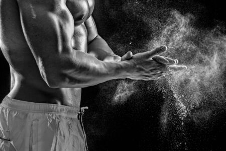 lower section view: young muscular man preparing to hand lifting heavy weight. White talcum dynamically scatters in different directions. Black and white. stands sideways. Close-up