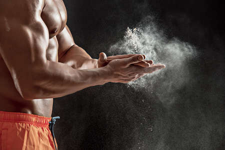 dynamically: young muscular man preparing to hand lifting heavy weight. White talcum dynamically scatters in different directions. stands sideways. Close-up