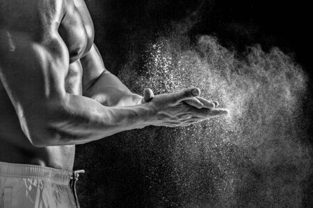 dynamically: young muscular man preparing to hand lifting heavy weight. White talcum dynamically scatters in different directions. Black and white. stands sideways. Close-up