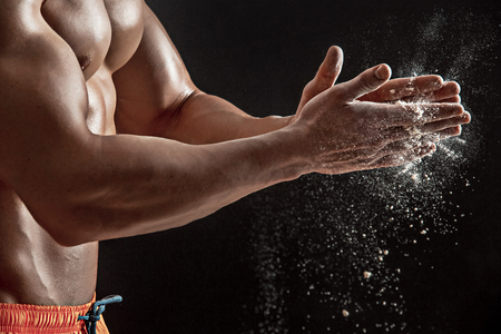 scatters: young muscular man preparing to hand lifting heavy weight. White talcum dynamically scatters in different directions. stands sideways. Close-up