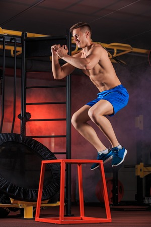 Shirtless man jumping on block. young muscular guy doing exercise jump CrossFit