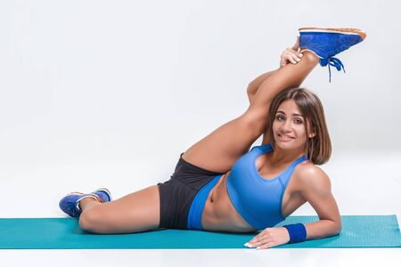 Sport and active lifestyle. Sporty flexible girl fitness woman in blue sportswear doing stretching exercise on light background. Stock Photo