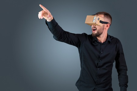 experiencing: Excited young man using a VR headset glasses and experiencing virtual reality on grey blue background