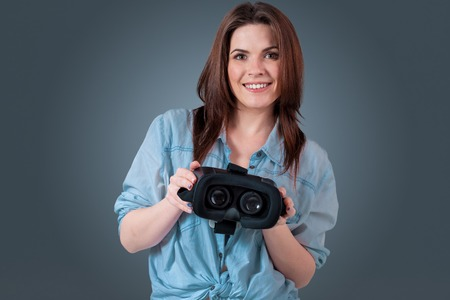 viewer: Excited young woman using a VR headset and experiencing virtual reality on grey blue background. She holds glasses for viewer