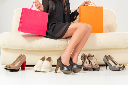 ankle strap: Beautiful legs. Woman trying many shoes. choosing. Sitting on the white sofa. Shopping. Stock Photo