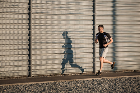 athletic wear: Full length portrait of athletic man running along beautiful grey wall outdoors, muscular build young runner working out while jogging in the park. Sunset Stock Photo