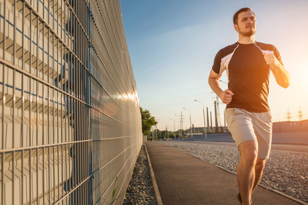 Close-up portrait of athletic man running along beautiful grey wall outdoors, muscular build young runner working out while jogging in the park. Sunset, with solar flare Stock Photo