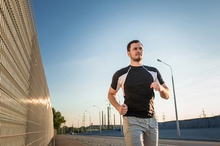 muscular build: Close-up portrait of athletic man running along beautiful grey wall outdoors, muscular build young runner working out while jogging in the park. Sunset Stock Photo