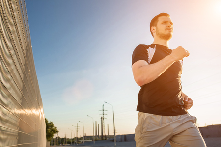 muscular build: Close-up portrait of athletic man running along beautiful grey wall outdoors, muscular build young runner working out while jogging in the park. Sunset, with solar flare Stock Photo