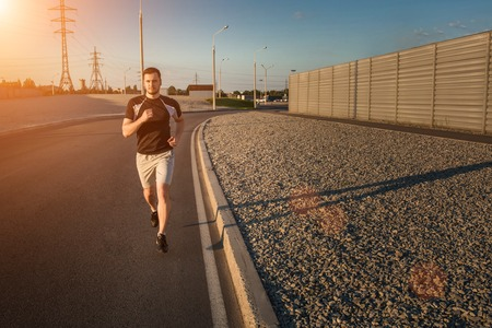 solar flare: Close-up portrait of athletic man running along beautiful grey wall outdoors, muscular build young runner working out while jogging in the park. Sunset, with solar flare Stock Photo