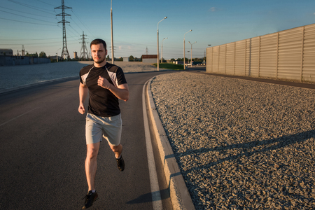 muscular build: Full length portrait of athletic man running along beautiful grey wall outdoors, muscular build young runner working out while jogging in the park. Sunset Stock Photo