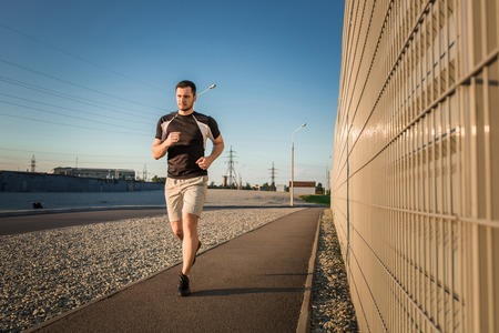 Close-up portrait of athletic man running along beautiful grey wall outdoors, muscular build young runner working out while jogging in the park. Sunset Stock Photo
