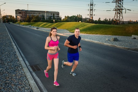 muscular build: Full length portrait of athletic couple running on the road, muscular build young runners working out while jogging in the park. Evening Stock Photo