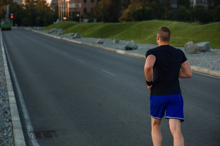 muscular build: Close-up portrait of athletic man running on the road, muscular build young runner working out while jogging in the park. Evening. view from the back Stock Photo