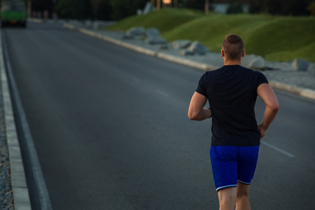 athletic wear: Close-up portrait of athletic man running on the road, muscular build young runner working out while jogging in the park. Evening. view from the back Stock Photo
