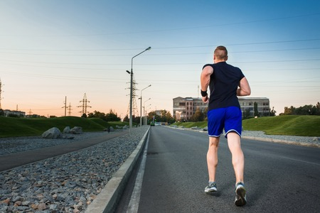 muscular build: Full length portrait of athletic man running on the road, muscular build young runner working out while jogging in the park. Evening. view from the back