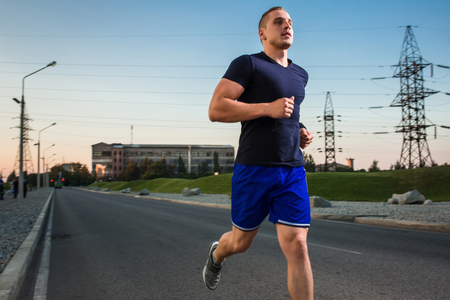 muscular build: Close-up portrait of athletic man running on the road, muscular build young runner working out while jogging in the park. Evening Stock Photo