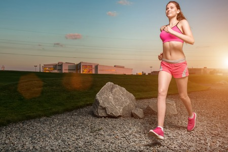 solar flare: Running woman. Runner jogging in sunny nature. Female fitness model training outside in sunset sky background. with solar flare Stock Photo