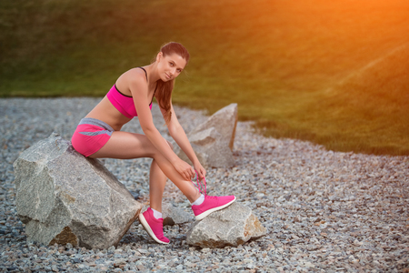 getting late: Running shoes - woman tying shoe laces. Female sport fitness runner getting ready for jogging outdoors on park path in late summer or fall.
