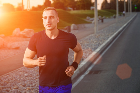 muscular build: Close-up portrait of athletic man running on the road, muscular build young runner working out while jogging in the park. sunset, with solar flare