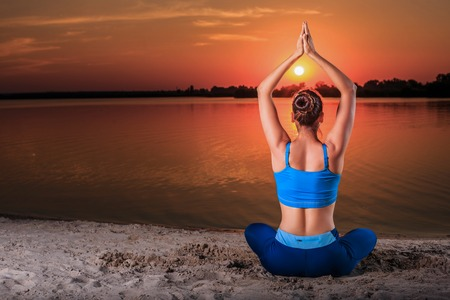 asanas: yoga at sunset on the beach. woman doing yoga, performing asanas and enjoying life on the river Stock Photo