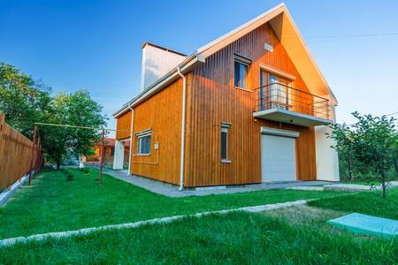 Prachtige houten huis met een gazon. Gevel van de traditionele huizen met gras op de voorgrond. bij zonsondergang en zonsopgang