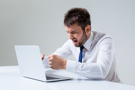 uses a computer: the young man is nervous and has a laptop. It uses a computer while sitting at a table. Office clothing Stock Photo