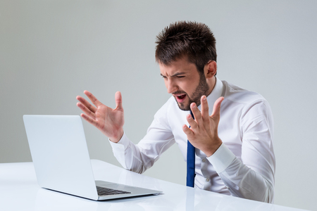 uses a computer: the young man is nervous. It uses a computer while sitting at a table. Office clothing Stock Photo