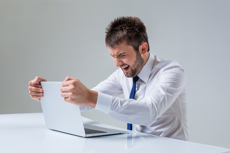 social emotional: young man emotional smiling and typing using laptop computer sitting at the table. Office clothing