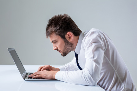 uses a computer: nerd young male typing on laptop. It uses a computer while sitting at a table. Office clothing Stock Photo