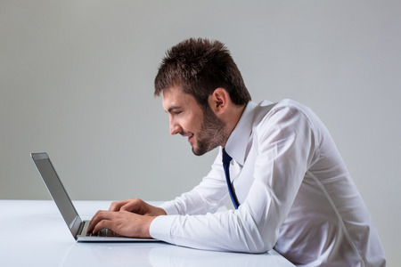 uses a computer: nerd young male smiling and typing on laptop. It uses a computer while sitting at a table. Office clothing