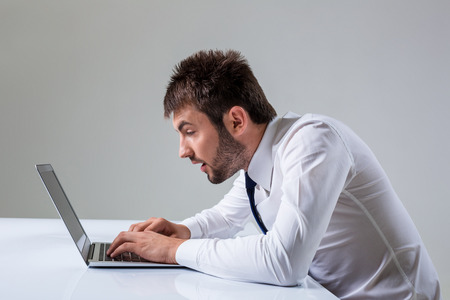 uses a computer: nerd young male surprise and typing on laptop. It uses a computer while sitting at a table. Office clothing Stock Photo