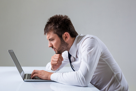 uses a computer: the young man stares at a laptop. It uses a computer while sitting at a table. Office clothing
