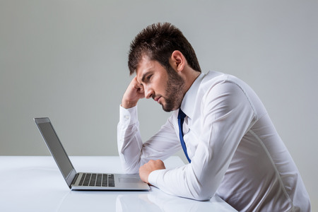 uses a computer: tired young man looking at laptop. It uses a computer while sitting at a table. Office clothing
