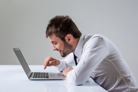 uses a computer: young man presses the keyboard on a laptop bully. It uses a computer while sitting at a table. Office clothing Stock Photo