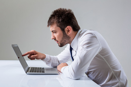 uses a computer: young man presses the laptop. It uses a computer while sitting at a table. Office clothing Stock Photo