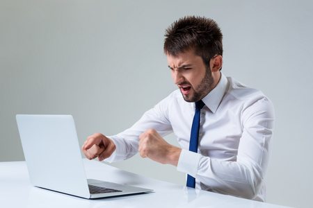 uses a computer: the young man is nervous and poke a finger. It uses a computer while sitting at a table. Office clothing