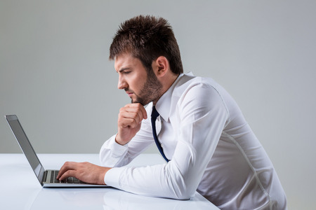 social emotional: the young man stares at a laptop. It uses a computer while sitting at a table. Office clothing