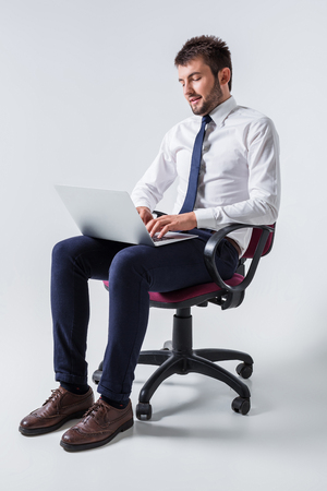 emotional young guy in office clothes working on a laptop computer and sitting on a chair Stock Photo