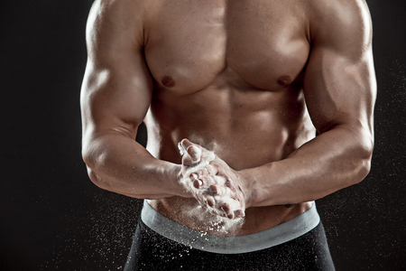 scatters: young muscular man preparing to hand lifting heavy weight. White talcum dynamically scatters in different directions. Close-up