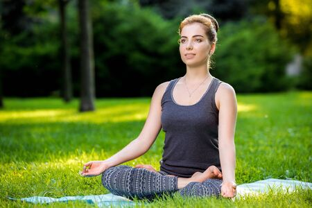 veda: Meditating woman in meditation in city park in yoga pose. Girl relaxing with serene relaxed expression outside in summer. Beautiful young Caucasian female model.