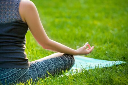 veda: Meditating woman in meditation in city park in yoga pose. Girl relaxing with serene relaxed expression outside in summer. Beautiful young Caucasian female model. Close up Stock Photo