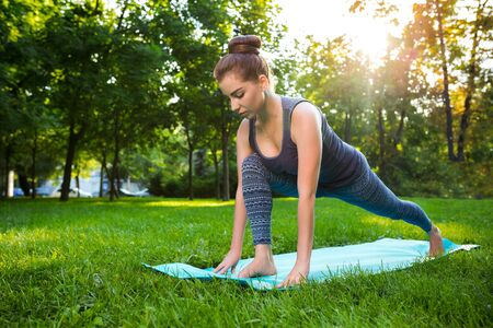 veda: Young fitness woman meditation in a city park.Yoga at sunset in the park. Girl is practicing yoga. Fitness training outdoors. Attractive fitness woman. Workout outdoors. Healthy lifestyle. sun flare